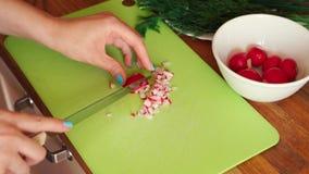 La donna sta affettando il ravanello fresco nella cucina sulla tavola di legno video d archivio
