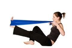 La donna sta allungando il suo piedino con una fascia di resistenza Fotografia Stock Libera da Diritti