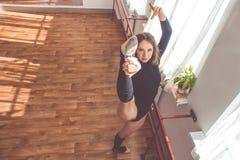 La donna sta allungando le sue gambe vicino al banco di balletto Fotografia Stock