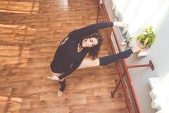 La donna sta allungando le sue gambe vicino al banco di balletto Fotografie Stock Libere da Diritti