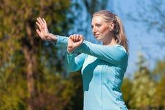 La donna sta allungando in un vestito da sport Immagini Stock