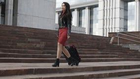 La donna sta andando con la valigia rossa stock footage