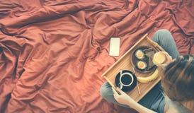 La donna sta avendo una prima colazione sana a letto Fotografie Stock Libere da Diritti