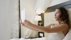 La donna sta avendo una video conversazione attraverso Internet sopra il suo pc della compressa mentre si trovava sul letto stock footage