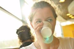 La donna sta bevendo dalla tazza di carta Fotografia Stock