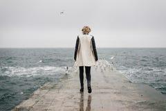 La donna sta camminando indietro sul pilastro e sta esaminando il mare Immagini Stock Libere da Diritti