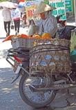 La donna sta caricando le verdure sulla sua bicicletta all'aperto in Vinh, Vietnam Fotografia Stock Libera da Diritti