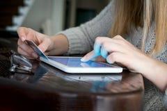 La donna sta comperando online con il pc della compressa fotografia stock