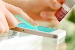La donna sta comperando online con il telefono cellulare immagine stock libera da diritti