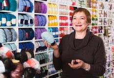 La donna sta comprando il filato variopinto per il loro hobby Immagine Stock Libera da Diritti