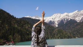 La donna sta con le sue mani su davanti al lago blu ed alle montagne innevate stock footage
