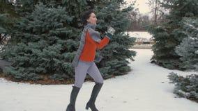 La donna sta correndo nella foresta dell'inverno, bello paesaggio con gli abeti nevosi