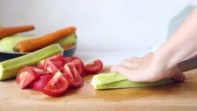 La donna sta cucinando Le mani delle donne hanno tagliato le verdure su un tagliere stock footage