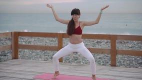 La donna sta eseguendo il asana di yoga, tenendo l'equilibrio, finente l'esercizio video d archivio