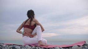 La donna sta eseguendo la torsione del corpo che si siede sul litorale, sulla pratica di yoga e su relativo alla ginnastica video d archivio