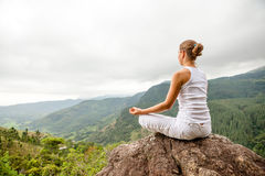 La donna sta facendo gli esercizi di yoga in montagne fotografie stock