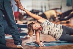 La donna sta facendo gli esercizi fisici durante la classe posturale della palestra fotografie stock