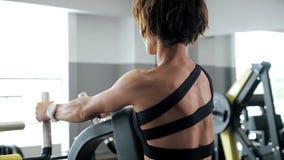 La donna sta facendo gli esercizi per i muscoli della spina dorsale sul vogatore, vista posteriore stock footage