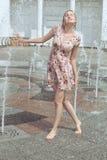 La donna sta giocando nella fontana con uno spruzzo Fotografia Stock