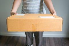 La donna sta inviando una scatola Immagine Stock