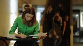 La donna sta lavorando con i modelli che coprono di foglie sopra le carte che correggono la seduta di numeri video d archivio