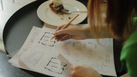 La donna sta lavorando con i modelli, disegni che si siedono nel caffè Sta correggendo i piani delle case archivi video