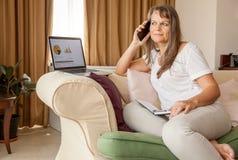 La donna sta lavorando dalla casa fotografie stock libere da diritti