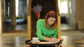 La donna sta lavorando dentro con i modelli che si siedono nel mezzo del corridoio del caffè davanti alle scale con la camminata  archivi video