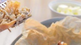 La donna sta mangiando il juliennes cotto in pasta è servito su un piatto sulla carta del panettiere con tè e burro Passa il prim archivi video