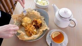 La donna sta mangiando il juliennes cotto in pasta è servito su un piatto sulla carta del panettiere con tè e burro Passa il prim stock footage
