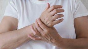 La donna sta massaggiando la sua mano Dolore unito stock footage