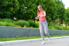 La donna sta pareggiando nel parco e controlla i suoi puls fotografia stock libera da diritti