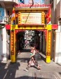 La donna sta passando dal portone buddista della via fotografia stock