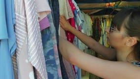 La donna sta passando in rassegna i vestiti ad un mercato di strada stock footage