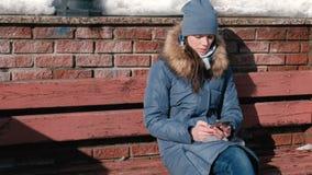 La donna sta passando in rassegna le pagine di Internet sul telefono cellulare che si siede nel parco dell'inverno archivi video