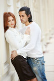La donna sta, pendendo alla parete e l'uomo la abbraccia Fotografia Stock