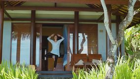 La donna sta praticando l'yoga nella posizione dell'albero, meditante ed i tratti, sul portico del bungalow sulla spiaggia in Bal stock footage