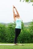 La donna sta praticando la mezzaluna laterale della luna di yoga Immagine Stock