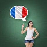 La donna sta precisando la bolla di pensiero con la bandiera del francese Fondo verde del bordo di gesso Immagini Stock