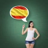 La donna sta precisando la bolla di pensiero con la bandiera dello Spagnolo Fondo verde del bordo di gesso Fotografia Stock
