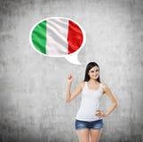 La donna sta precisando la bolla di pensiero con la bandiera italiana Fondo concreto Immagini Stock Libere da Diritti
