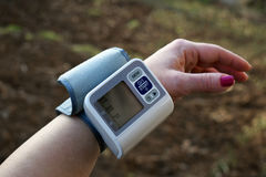 La donna sta prendendo la cura per salute con il monitor e la pressione sanguigna del battito del focolare Fotografie Stock