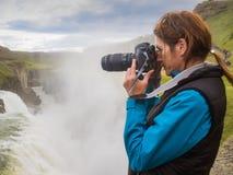 La donna sta prendendo un'immagine ad una cascata di Gullfoss - Islanda Immagini Stock