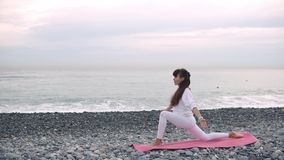 La donna sta rilassandosi in asanas di yoga sulla riva di mare del ciottolo a tempo la mattina archivi video