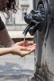 La donna sta rinfrescando alla fontana nei giorni caldi fare caldissimo Immagini Stock Libere da Diritti