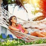 La donna sta riposando nell'amaca sotto le palme sul tropicale Immagine Stock Libera da Diritti