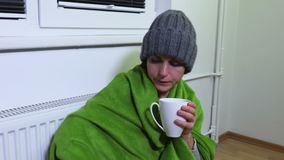 La donna sta scaldandosi al radiatore di riscaldamento archivi video