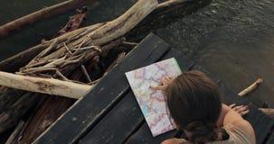 La donna sta scegliendo il posto per visitare sulla mappa che riposa sul pilastro del mare al tramonto stock footage