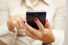 La donna sta scrivendo sullo schermo attivabile al tatto sul grande telefono cellulare Immagine Stock Libera da Diritti
