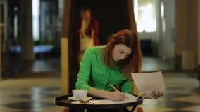 La donna sta sedendosi in caffè che lavora con i modelli che coprono di foglie sopra le carte che correggono i numeri stock footage